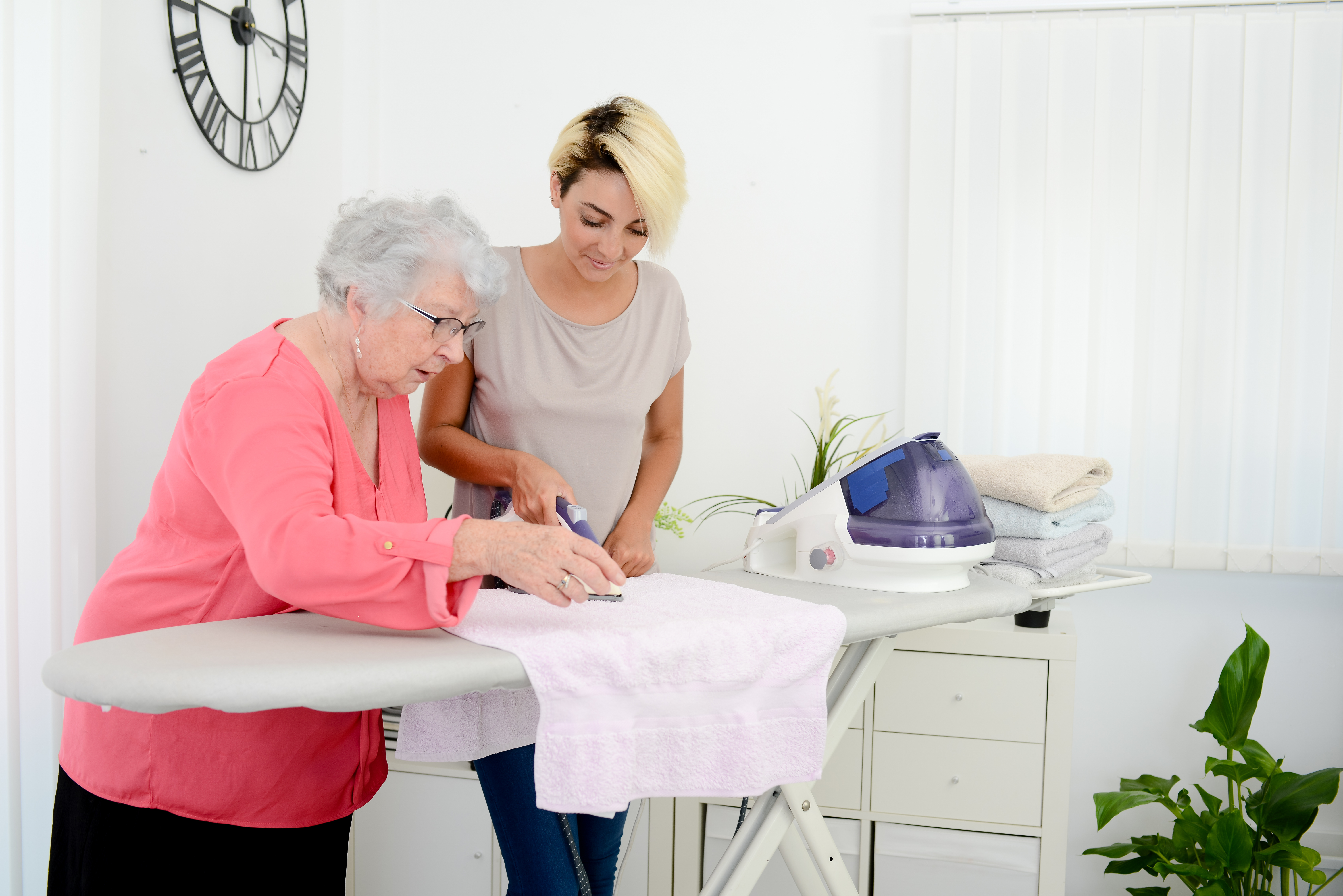 cheerful young girl ironing and helping with household chores elderly woman at home